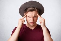 Studio shot of sullen Caucasian male frowns face, keeps fore fingers on temples, has discontent expression, poses against white ba. Ckground. People, facial Stock Image