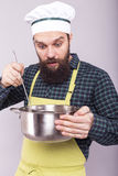 Studio shot of a surprised man tasting soup with a ladle Stock Photography