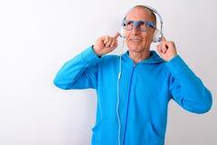 Studio shot of thoughtful happy bald senior man smiling while li. Stening to music and wearing eyeglasses against white background stock photos