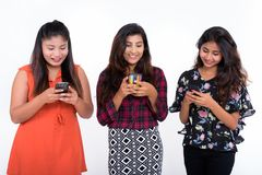 Studio shot of three happy young Persian woman friends smiling w stock photo