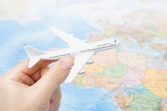Studio shot of toy plane in hand with world map on background - focus on the plane Stock Photos