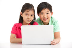 Studio Shot Of Two Chinese Children With Laptop Royalty Free Stock Image