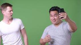 Two young multi-ethnic handsome men together against green background. Studio shot of two young multi-ethnic handsome men together against chroma key with green stock footage