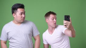 Two young multi-ethnic handsome men together against green background. Studio shot of two young multi-ethnic handsome men together against chroma key with green stock video