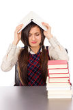 Studio shot of unhappy student with book on the head sitting at Royalty Free Stock Photography