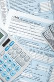 Studio shot of United States of America Tax Form 1040 with calculator and US dollars over it. Studio shot of Tax Form 1040 with calculator and US dollars over it Royalty Free Stock Images