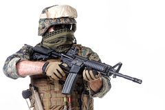 US Marine Soldier. Studio shot of United States Marine with rifle weapons in uniforms. Military equipment, army helmet, combat boots, tactical gloves. Isolated Royalty Free Stock Photo