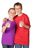 Studio shot on white of brother and sister drinking milk royalty free stock images