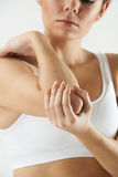 Studio Shot Of Woman With Painful Elbow Stock Photo