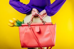 Studio shot of a woman wearing spring outfit and holding a bag with yellow tulips Stock Photos