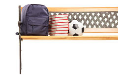 Studio shot of a wooden bench with books, school bag and soccerb Royalty Free Stock Images