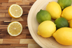 Studio shot of a wooden bowl filled with lemons and limes Royalty Free Stock Image