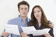 Studio Shot Of Worried Couple Looking At Bills Stock Images