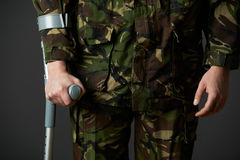 Studio Shot Of Wounded Soldier Using Crutch Royalty Free Stock Photos