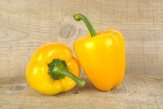 Studio shot of yellow bell peppers on wooden plank Stock Photos
