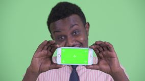 Face of happy young African businessman showing phone. Studio shot of young African businessman with Afro hair against chroma key with green background stock video footage
