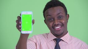 Face of happy young African businessman showing phone. Studio shot of young African businessman with Afro hair against chroma key with green background stock footage