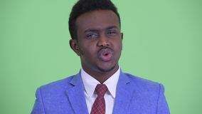 Face of serious young African businessman nodding head no. Studio shot of young African businessman with Afro hair wearing suit against chroma key with green stock video footage
