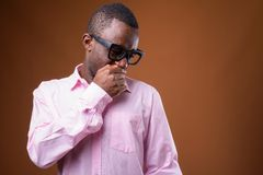 Portrait of young African businessman looking disgusted. Studio shot of young African businessman wearing pink shirt against brown background royalty free stock image