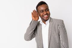 Portrait of happy young African businessman thinking and listening. Studio shot of young African businessman wearing suit against white background stock image