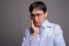 Young Asian man doctor wearing eyeglasses against gray backgroun. Studio shot of young Asian man doctor wearing eyeglasses against gray background royalty free stock image