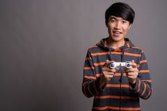 Young Asian man playing games against gray background stock photography