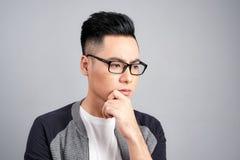 Studio shot of young Asian man thinking while wearing eyeglasses.  stock photo