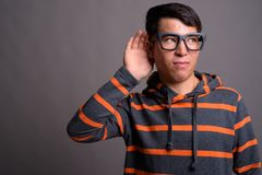 Young Asian nerd man wearing hoodie against gray background stock photos