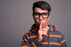 Young Asian nerd man wearing hoodie against gray background royalty free stock photos