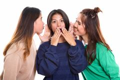 Studio shot of young Asian woman looking shocked with both frien. Studio shot of young Asian women looking shocked with both friends whispering on each side stock photo