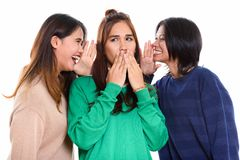 Studio shot of young Asian woman looking shocked with both frien. Studio shot of young Asian women looking shocked with both friends whispering on each side royalty free stock image