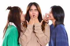 Studio shot of young Asian woman looking shocked with both frien. Studio shot of young Asian women looking shocked with both friends whispering on each side royalty free stock photography