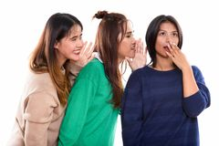 Studio shot of young Asian woman looking shocked with both frien. Studio shot of young Asian women looking shocked with both friends whispering on one side royalty free stock photography