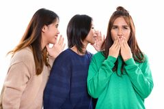 Studio shot of young Asian woman looking shocked with both frien. Studio shot of young Asian women looking shocked with both friends whispering on one side royalty free stock image
