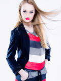 Studio shot of a young and attractive female model showing confidence wearing a stripe blouse and black jacket. Vertical color image. Studio shot of a young and royalty free stock photography