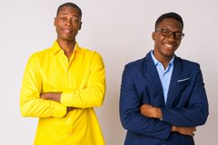 Two young happy African businessmen smiling with arms crossed together stock images