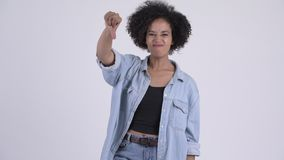 Young angry African woman giving thumbs down