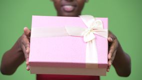Young happy African woman giving gift box. Studio shot of young beautiful African woman against chroma key with green background stock video