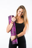Studio shot of young beautiful blonde woman holding yoga mat and posing ready for gym Royalty Free Stock Images