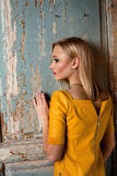 Studio shot of young and beautiful girl standing near old door in yellow leather dress wearing in studio. Blonde girl Royalty Free Stock Photo