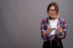 Young beautiful Kazakh woman against gray background. Studio shot of young beautiful Kazakh woman wearing checkered shirt against gray background Royalty Free Stock Images