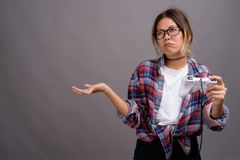 Young beautiful Kazakh woman against gray background. Studio shot of young beautiful Kazakh woman wearing checkered shirt against gray background Stock Images