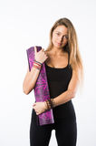 Studio shot of young beautiful teenage girl holding yoga mat and posing ready for gym Royalty Free Stock Photography