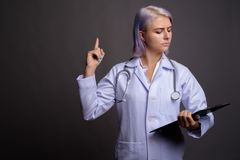 Young beautiful woman doctor with short colorful hair against gr stock image