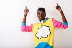 Studio shot of young black African man pointing both fingers up. While posing with headphones around neck against white background royalty free stock photo