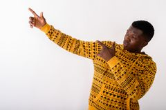Studio shot of young black African man pointing both fingers up. Against white background stock images