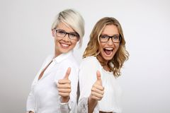 Two young blonde women smiling thumbs up royalty free stock images
