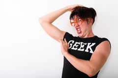 Studio shot of young funny nerd man looking disgusted while smel. Ling armpit and wearing eyeglasses against white background royalty free stock photos