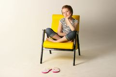 Studio shot of a young girl sitting on yellow chair. Dreaming young girl sitting on yellow chair. Shot of a little girl relaxing on a chair at home Royalty Free Stock Photo