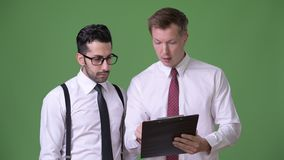 Two young multi-ethnic businessmen working together against green background. Studio shot of young handsome bearded Persian businessman and young handsome stock video